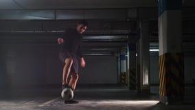 Untertageparkplatz Ein Fußballmann, der seine Fußballfähigkeiten ausbildet Treten des Balls von der Wand stock video