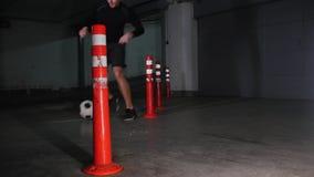 Untertageparkplatz Ein Fu?ballmann, der seine Fu?ballf?higkeiten ausbildet F?hrung der ums?umenden Hindernisse des Balls stock video footage
