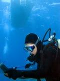 Unterwasseratemgerät-Taucher, der Lehren unter dem Boot überprüft Stockbild