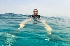 Unterwasseratemgerättaucher auf Oberfläche vor Sturzflug Lizenzfreie Stockfotos