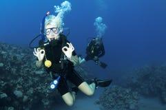 Unterwasseratemgerättaucher geben OKAYzeichen Stockbild