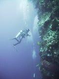 Unterwasseratemgerättaucher gegen Klippe Stockfoto