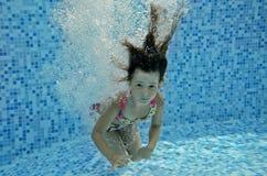 Unterwasserkind springt zum Swimmingpool Stockbild