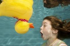 Unterwasserschwimmen des kleinen Mädchens mit Gummiente Lizenzfreies Stockbild