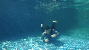 Unterwasserschwimmen im Swimmingpool stock video