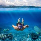 Unterwassertrieb eines jungen Mannes, der an in einem tropischen Meer schnorchelt lizenzfreies stockbild