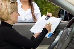 Unterzeichnen des Abkommens auf einem Neuwagen Lizenzfreie Stockfotografie