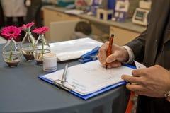 Unterzeichnen eines Vertrages auf einer Messe Stockbild