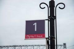 Unterzeichnen Sie Bahnhof OM mit der Aufschrift auf russisches und englisch - erste Bahn Stockfotos
