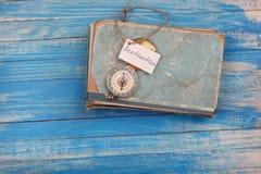 Unterzeichnen Sie Bestimmungsort und Kompass auf altem Buch - Weinleseart Stockfotografie