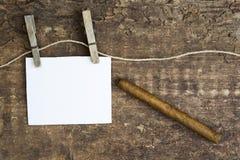 Unterzeichnen Sie das Hängen an der Wäscheleine auf hölzernem Hintergrund mit einer Zigarre Lizenzfreie Stockbilder