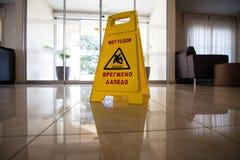 Unterzeichnen Sie das Zeigen des Warnens des nassen Bodens der Vorsicht auf nassem Fliesenboden im Sonnenuntergang Stockbilder