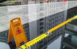 Unterzeichnen Sie das Zeigen des Warnens des nassen Bodens der Vorsicht und kümmern Sie sich den um Schritt Stockbilder