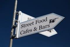 Unterzeichnen Sie das Zeigen in Richtung zum Straßenlebensmittel, -cafés und -stangen Stockfotografie