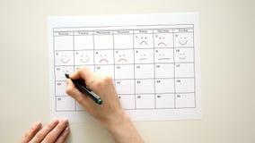 Unterzeichnen Sie den Tag im Kalender mit einem Stift, zeichnen Sie ein Lächeln stock video footage