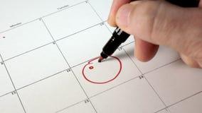 Unterzeichnen Sie den Tag im Kalender mit einem Stift, zeichnen Sie ein Lächeln stock footage