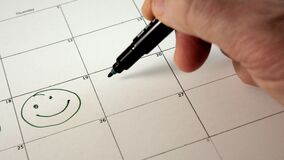 Unterzeichnen Sie den Tag im Kalender mit einem Stift, zeichnen Sie ein Lächeln