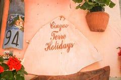Unterzeichnen Sie die Förderung von Cinque Terre Holidays im scrit auf der wal Terrakotta stockbilder