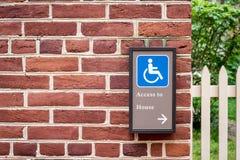 Unterzeichnen Sie die Richtung des Handikaps, das an einer Backsteinmauer angebracht wird stockbilder