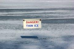 Unterzeichnen Sie die Warnung des gefährlichen dünnen Eises und über dem gefrorenen See hängen Lizenzfreie Stockfotografie