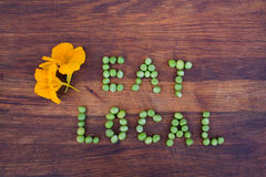"""Unterzeichnen Sie """"Eat Localâ€-, das von den grünen Erbsen auf hölzernem Hintergrund gemacht wird lizenzfreie stockbilder"""