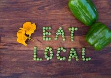 """Unterzeichnen Sie """"Eat Localâ€-, das von den grünen Erbsen auf hölzernem Hintergrund gemacht wird stockbilder"""