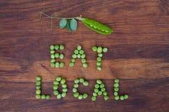 """Unterzeichnen Sie """"Eat Localâ€-, das von den grünen Erbsen und von der Erbsenhülse mit Blättern auf hölzernem Hintergrund gema stockfotografie"""