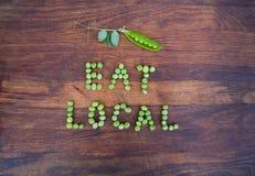 """Unterzeichnen Sie """"Eat Localâ€-, das von den grünen Erbsen und von der Erbsenhülse mit Blättern gemacht wird stockfotos"""