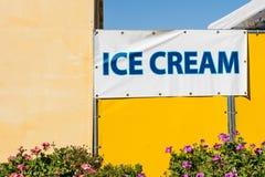 Unterzeichnen Sie für Eiscreme auf einer gelben Wand an einem hellen sonnigen Sommertag Lizenzfreie Stockfotos