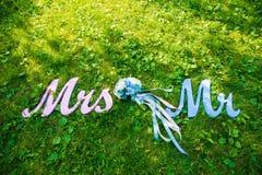Unterzeichnen Sie für Heirats` Herrn u. Frau ` Herr und missis mit Blumen im Gras lizenzfreie stockfotografie