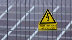 Unterzeichnen Sie mit der Wörter Hochspannung - Lebensgefahr auf Deutsch vor Sonnenkollektoren Lizenzfreie Stockfotografie