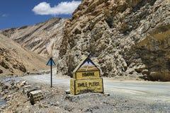 Unterzeichnen Sie nahe gelegene Straße des LÄCHELNS BITTE Gebirgsin Ladakh Stockfotografie