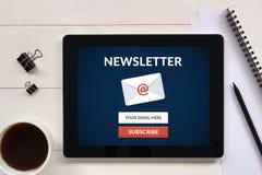 Unterzeichnen Sie Newsletterkonzept auf Tablettenschirm mit Bürogegenstand lizenzfreies stockbild