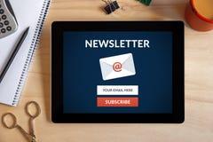Unterzeichnen Sie Newsletterkonzept auf Tablettenschirm mit Bürogegenstand Lizenzfreie Stockbilder