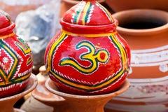 Unterzeichnen Sie OM auf dem roten Topf durch die indischen Handwerker Stockfotos