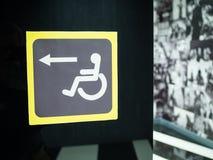 Unterzeichnen Sie Zeichen für behindertes auf einem schwarzen Hintergrund Stockfotografie
