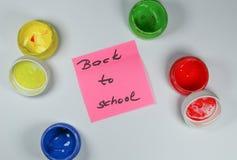 Unterzeichnen Sie, zurück zu Schule-` auf weißem Hintergrund mit Farbenfarben lizenzfreies stockbild