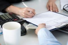 Unterzeichnende Dokumente der Frau für eine Reihe von hundert Dollarscheinen Lizenzfreies Stockfoto