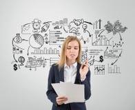 Unterzeichnende Dokumente der Geschäftsfrau nahe grauer Wand Lizenzfreie Stockfotografie