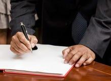 Unterzeichnende Dokumente des Mannes Stockfotos