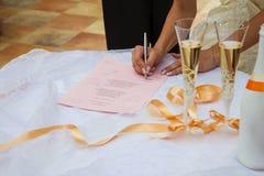Unterzeichnende Heiratsurkunde. Hochzeits-Champagne-Gläser. Heirat - Feier der Liebe stockbilder
