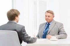 Unterzeichnende Papiere des älteren Mannes und des jungen Mannes im Büro Lizenzfreie Stockbilder