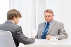 Unterzeichnende Papiere des älteren Mannes und des jungen Mannes im Büro Stockfoto