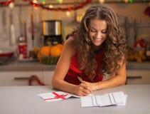 Unterzeichnende Postkarten der glücklichen jungen Hausfrau Weihnachtsin der Küche Stockfotografie