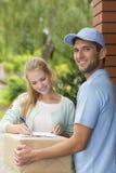 Unterzeichnender Eingang des Kunden der Kastenlieferung durch lächelnden Kurier mit blauer Kappe stockfotos