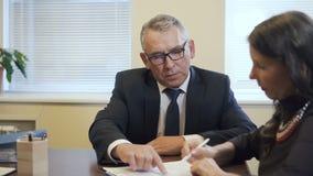 Unterzeichnender Versicherungsvertrag der reifen Frau und älterer Rechtsanwalt, die es überprüfen stock video footage