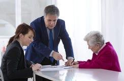 Unterzeichnender Versicherungsvertrag und Spende der Großmutter zu ihrem gran Stockfoto
