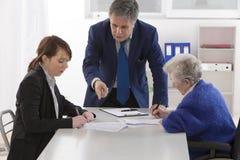 Unterzeichnender Versicherungsvertrag und Spende der Großmutter zu ihrem gran Lizenzfreie Stockfotografie