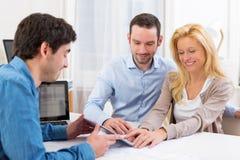 Unterzeichnender Vertrag der jungen attraktiven Paare auf Tablette Lizenzfreies Stockbild