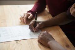 Unterzeichnender Vertrag des Afroamerikanermannes, Kundenpaar setzte Zeichen stockbilder
